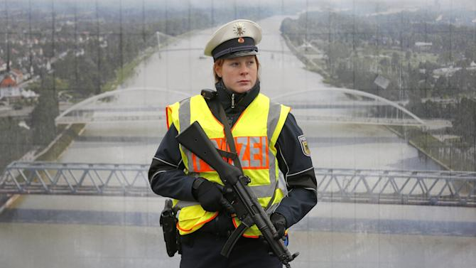 A German police officer stands in front of a poster with a picture of the Rhein river as she takes part in a control at French-German border in Strasbourg