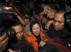 Banten governor Chosiyah, wearing an KPK orange vest, walks as she is detained at the KPK office in Jakarta