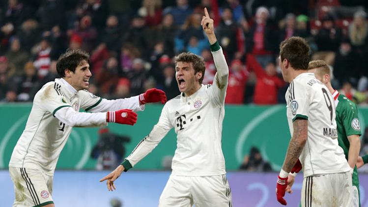 Bayern's Thomas Mueller, center, celebrates with teammates Mario Mandzukic of Croatia, right, and Javier Martinez of Spain after scoring his side's second goal during the German soccer cup third round match between FC Augsburg and FC Bayern Munich in Augsburg, southern Germany, Wednesday, Dec. 4, 2013