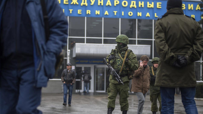 Unidentified armed man patrols a square in front of the airport in Simferopol, Ukraine, Friday, Feb. 28, 2014. Dozens of armed men in military uniforms without markings patroled the airport in the capital of Ukraine's strategic Crimea region on Friday as tensions in the country's Russian-speaking southeast escalated. (AP Photo/Andrew Lubimov)