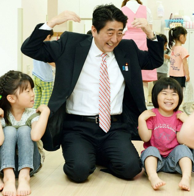 Japan's Prime Minister Shinzo Abe plays with children as he inspects a daycare center in Yokohama