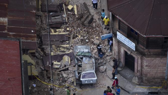 Residents walk among rubble after a magnitude 7.4 earthquake struck in San Marcos, Guatemala, Wednesday Nov. 7, 2012. The mountain village, some 80 miles (130 kilometers) from the epicenter, suffered much of the damage with some 30 homes collapsing in its center. There are three confirmed dead and many missing after the strongest earthquake to hit Guatemala since a deadly 1976 quake that killed 23,000. (AP Photo/Moises Castillo)