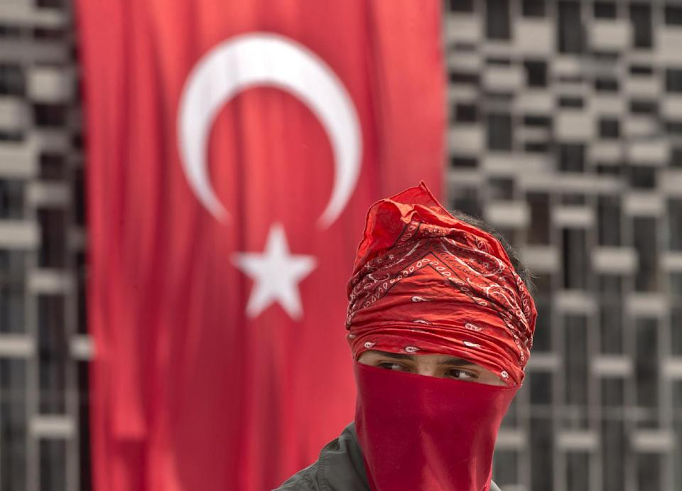 FILE - In this Wednesday, June 12, 2013, file photo, a masked protester is backdropped by a Turkish flag on the edge of Gezi Park, in Istanbul, Turkey. (AP Photo/Vadim Ghirda, File)