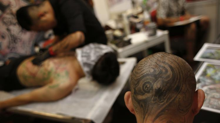 A man with tattoo on his head sits inside a booth at the International Hong Kong China Tattoo Convention in Hong Kong
