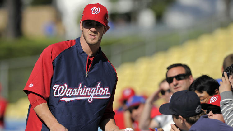 Washington Nationals left fielder Bryce Harper signs autographs for fans prior to their baseball game against the Los Angeles Dodgers, Saturday, April 28, 2012, in Los Angeles. (AP Photo/Mark J. Terrill)