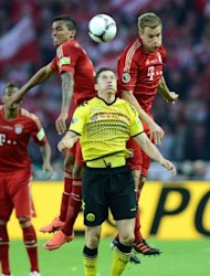 Bayern Munich's defenders Breno (L) and Holger Badstuber (R) jumps for the ball with Dortmund's striker Robert Lewandowski during the German cup final football match at the Olympiastadion in Berlin. Bundesliga champions Borussia Dortmund blasted Champions League finalists Bayern Munich 5-2
