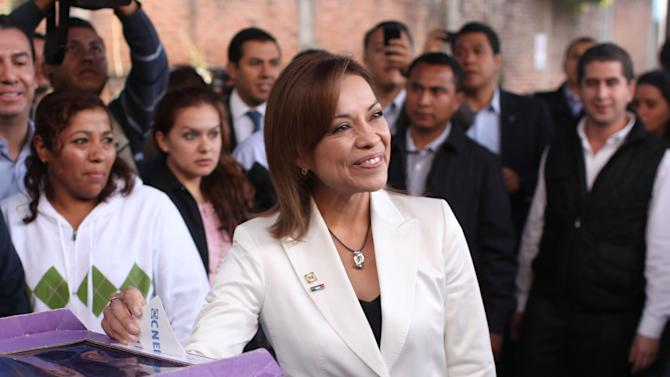 Josefina Vasquez Mota, center, presidential candidate of Mexico's National Action Party, PAN, casts her vote during the party's primary elections in Huixquilucan, Mexico, Sunday, Feb. 5, 2012. If nominated Vasquez Mota would be the first woman of a major political party to run for Mexico's highest office. (AP Photo/Alexandre Meneghini)