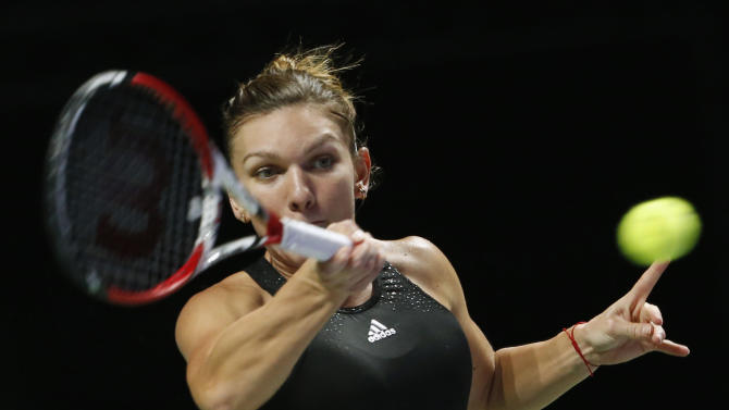 Simona Halep of Romania hits a return to Agnieszka Radwanska of Poland during their WTA Finals singles semi-final tennis match at the Singapore Indoor Stadium