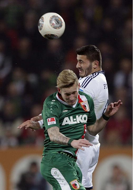 Augsburg's Andre Hahn, foreground, and Schalke's Sead Kolasinac challenge for the ball during the German first division Bundesliga soccer match between FC Augsburg and FC Schalke 04, in Augsbu