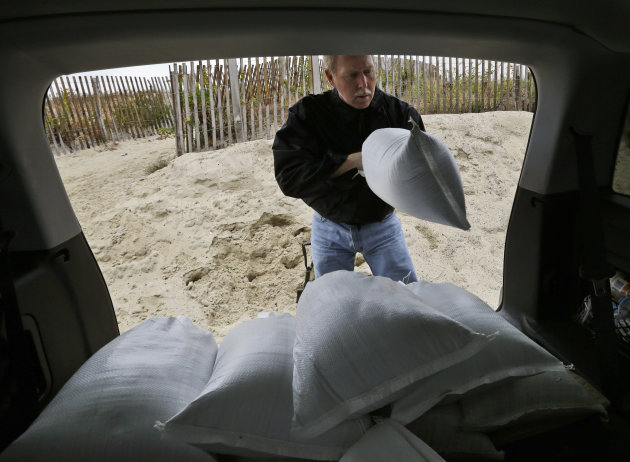Mike Strobel loads sand bags for his business, Mike's Carpet Connection, as Hurricane Sandy bears down on the East Coast, Sunday, Oct. 28, 2012, in Fenwick Island, Del. Tens of thousands of people were ordered to evacuate coastal areas Sunday as big cities and small towns across the U.S. Northeast braced for the onslaught of a superstorm threatening some 60 million people along the most heavily populated corridor in the nation. (AP Photo/Alex Brandon)