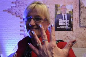 Martine, a 54-year-old France's far-right National Front political party political activist, shows her nails painted with the French national flag at the FN headquarters in Henin Beaumont