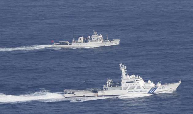 In this photo released by Japan Coast Guard, a Japan Coast Guard vessel, bottom, sails along with a Chinese fisheries patrol boat near disputed islands, called Senkaku in Japan and Diaoyu in China, in the East China Sea Tuesday, Sept. 18, 2012. The Coast Guard vessel issued a warning to the vessel near the islands early Tuesday. (AP Photo/Japan Coast Guard)