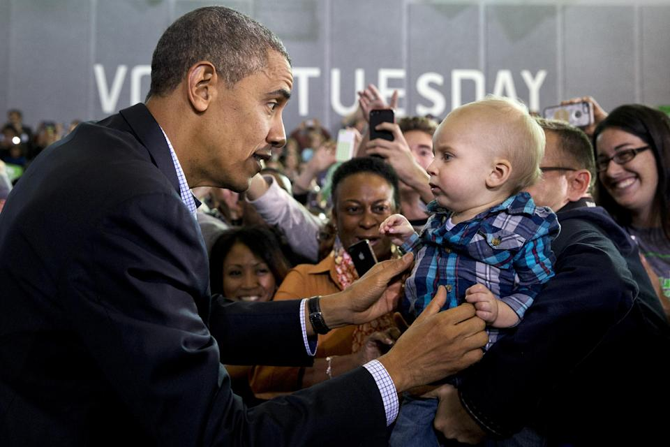 President Barack Obama reaches to hold a baby before speaking at a campaign event for Virginia Democratic gubernatorial candidate Terry McAuliffe at Washington-Lee High School in Arlington, Va. on Sunday, Nov. 3, 2013. (AP Photo/Jacquelyn Martin)