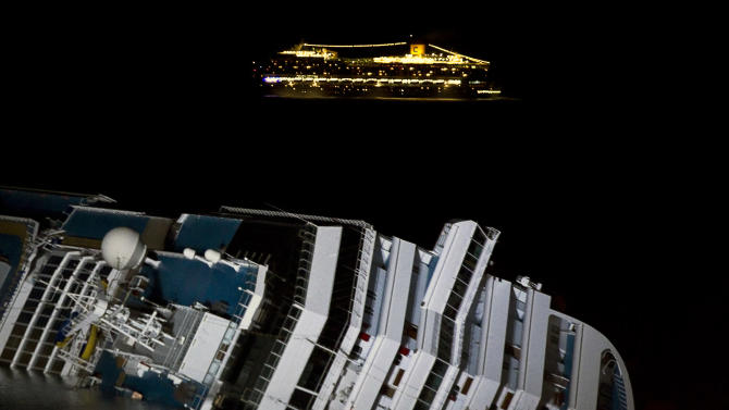 The cruise ship Costa Serena passes offshore as its sister ship Costa Concordia lies on its side off the tiny Tuscan island of Giglio, Italy, Wednesday, Jan. 18, 2012. The $450 million Costa Concordia cruise ship was carrying more than 4,200 passengers and crew when it slammed into a reef Friday off the tiny Italian island of Giglio after the captain made an unauthorized maneuver. The death toll stands at 11, with 22 people still missing. (AP Photo/Angelo Carconi)