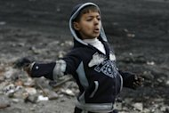 "A Palestinian boy prepares to throw a stone at Israeli forces during clashes in the Shufat refugee camp in Jerusalem. Children as young as 12 were made to choose a ""political affiliation"" by which they were grouped in prison"