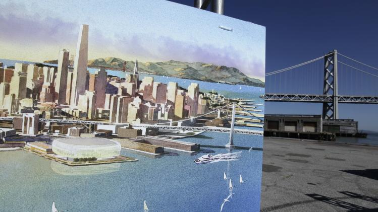 An artists sketch showing the Golden State Warriors proposed new basketball arena is displayed with the San Francisco-Oakland Bay Bridge in the background in San Francisco, Tuesday, May 22, 2012. The Warriors unveiled plans to build an arena at Piers 30-32. The waterfront site  is just blocks from the San Francisco Giants' ballpark and the downtown financial district. The arena is expected to be completed by 2017. (AP Photo/Eric Risberg)