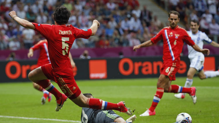 Greece goalkeeper Michalis Sifakis, bottom,  stops Russia's Yuri Zhirkov during the Euro 2012 soccer championship Group A  match between Greece and Russia in Warsaw, Poland, Saturday, June 16, 2012. (AP Photo/Matt Dunham)