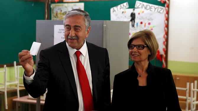 Turkish Cypriot presidential hopeful Mustafa Akinci with his wife Meral casts his vote at a polling station in northern Nicosia