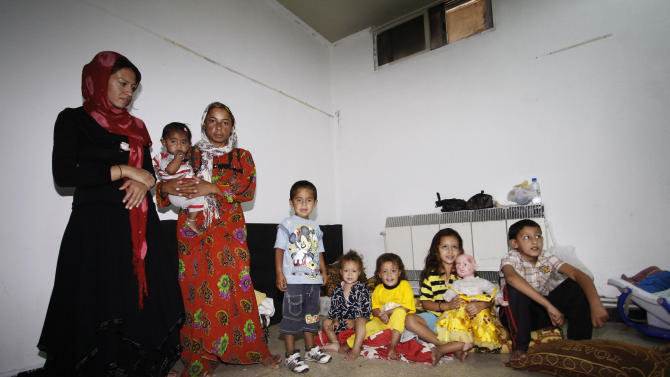 Syrians, who fled their homes due to fighting between Syrian rebels and government forces, take refuge at the Samiya al-Makhzumi school in Mezzeh neighborhood, in Damascus, Syria, Sunday, Sept. 16, 2012. Many Syrians who have fled violence in their country are living near the border but outside the dozen camps, either staying with relatives, renting apartments, and in some cases take refuge at schools. The influx since the uprising against Syrian President Bashar Assad began 18 months ago has raised concerns about sectarian tension and militant activity in the region. (AP Photo/Muzaffar Salman)