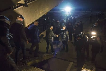 Ukraine's President Petro Poroshenko shakes hands with a Ukrainian POW returning home after being exchanged for pro-Russian separatist prisoners, in Kiev