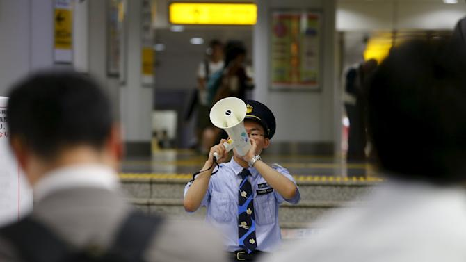 Station staff member makes announcement as passengers wait for re-opening of Shinkansen bullet trains gates at Tokyo station in Tokyo