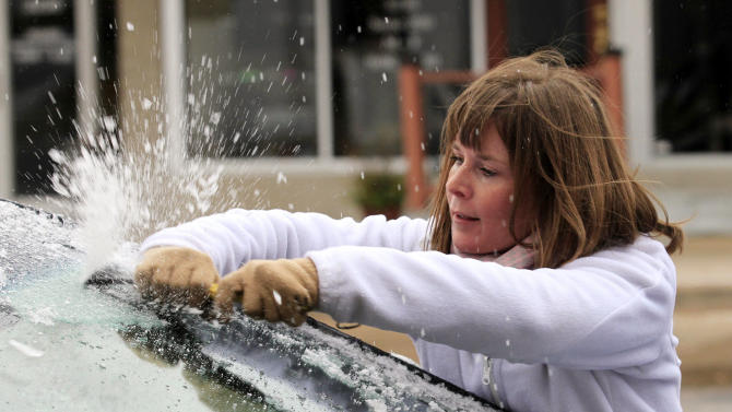 Krystal Wright scrapes ice from her car's windshield Friday, Nov. 27, 2015 in Wichita, Kan. The winter weather left a layer of ice on roads and cars early Friday morning after a heavy rain on Thanksgiving day that set a record with over 2 inches of rain. Brian Corn/The Wichita Eagle via AP)