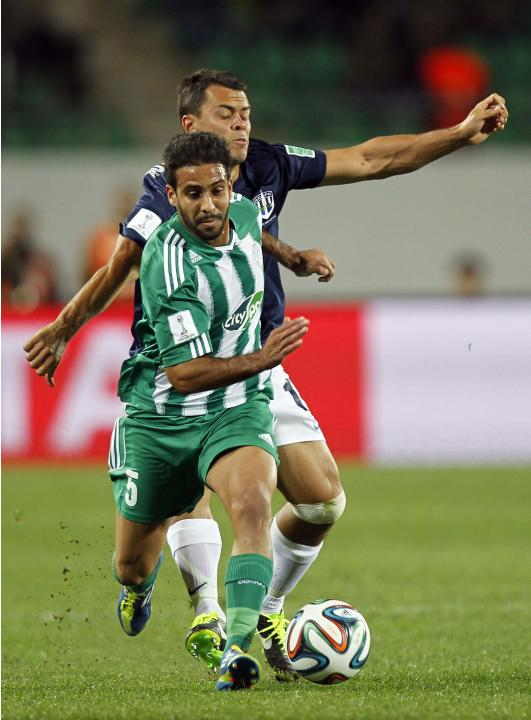 Moutaouali of Raja Casablanca fights for the ball with Marquez of Auckland City FC during their FIFA Club World Cup soccer match at Agadir Stadium in Agadir