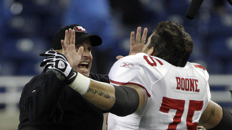 San Francisco 49ers head coach Jim Harbaugh, left, and offensive tackle Alex Boone (75) celebrate their 25-19 win over the Detroit Lions after an NFL football game in Detroit, Sunday, Oct. 16, 2011. (AP Photo/Carlos Osorio)