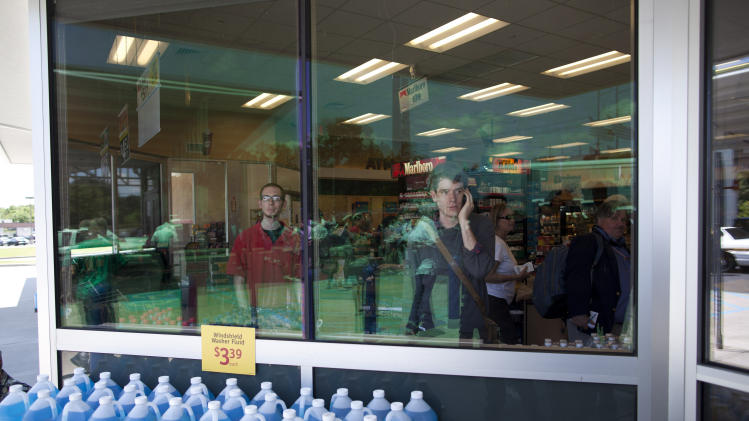 Customers look on as Republican presidential candidate, former Massachusetts Gov. Mitt Romney arrives for a stop at Wawa gas station  in Quakertown, Pa., Saturday, June 16, 2012.  (AP Photo/Evan Vucci)
