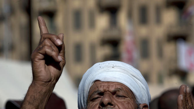 An Egyptian protester opposing president Mohammed Morsi attends Friday prayers at Tahrir Square, Cairo, Egypt, Friday, Dec. 7, 2012. Thousands of Egyptians took to the streets after Friday midday prayers in rival rallies and marches across Cairo, as the standoff deepened over what opponents call the Islamist president's power grab, raising the specter of more violence. (AP Photo/Nasser Nasser)