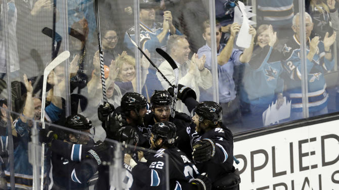 San Jose Sharks center Patrick Marleau center, is mobbed by teammates after scoring the game-winning goal against the Vancouver Canucks during overtime of Game 4 of their first-round NHL hockey Stanley Cup playoff series in San Jose, Calif., Tuesday, May 7, 2013. San Jose won 4-3 in overtime. (AP Photo/Marcio Jose Sanchez)