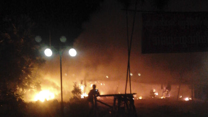 In this early Nov. 29, 2012 photo provided by a monk, flames are seen at the gate of Chinese mining partner Wan Bao where protesters camped before the police crackdown in Monywa, northwestern Myanmar. Security forces cracked down on protesters occupying a copper mine, a joint venture between the Chinese firm and a company controlled by Myanmar's military, early Thursday, using water cannons and other devices to break up the rally hours before opposition leader Aung San Suu Kyi was expected to hear their grievances. Dozens of Buddhist monks and villagers were injured, according to several protesters. Those who fled the site emerged with burns and charred clothing on their bodies. (AP Photo) EDITORIAL USE ONLY