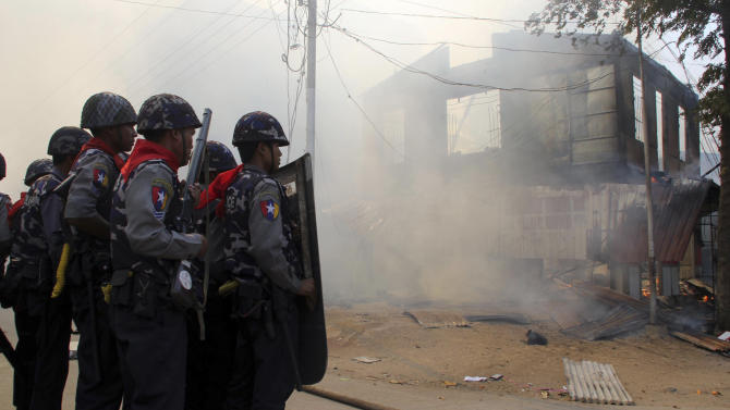 FILE - In this Thursday, March 21, 2013 file photo, armed Myanmar police officers provide security around a smoldering building following ethnic unrest between Buddhists and Muslims in Meikhtila, Mandalay division, about 550 kilometers (340 miles) north of Yangon, Myanmar. Few imagined Myanmar would embrace democracy when the U.S. began its historic engagement with the military regime. The country's rapid changes were lauded by visiting Western leaders, and the nation's president was hailed as a hero. But spasms of spreading, communal violence show the reform path is bumpier that expected and have taken the sheen off a foreign policy success of the Obama administration's first term. (AP File Photo)