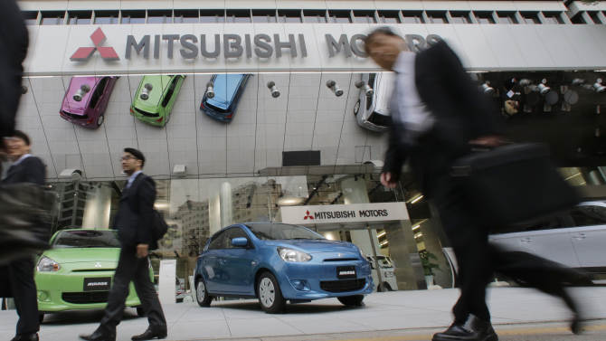 People walk by the headquarters of the Mitsubishi Motors Corp. in Tokyo, Tuesday, Oct. 30, 2012. Mitsubishi Motors Corp.'s fiscal second-quarter net profit improved 60 percent to 10.1 billion yen ($126 million) on cost cuts, but the Japanese automaker lowered its projection Tuesday for China, where a bitter territorial dispute is sending sales plunging. Mitsubishi, which reported a 6.3 billion yen profit for the July-September period the previous year, is among the Japanese automakers making a solid recovery after last year's earthquake and tsunami disaster that disrupted supply chains. (AP Photo/Shizuo Kambayashi)
