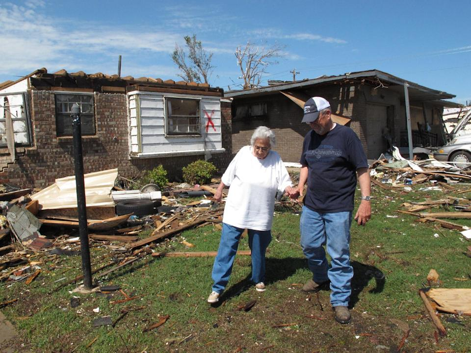 In this Thursday, May 23, 2013 photo, Eldon Parrish helps his mother, Shirley, across the debris-strewn lawn of her home in Moore, Okla. The 80-year-old woman escaped to a neighbor's shelter just minutes before Monday's EF5 tornado destroyed her home. (AP Photo/Allen Breed)