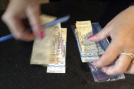 Cheryl Cohen handles tickets from a canceled 1979 concert by The Who, which were exchanged by fans for their upcoming Quadrophenia tour concert in February 2013,at the Dunkin Donuts Center in Providence, R.I., Tuesday, July 31, 2012. The 1979 concert was cancelled due to safety concerns after 11 people died in a stampede before a show in Ohio. The arena honored the tickets for that canceled show, which will be auctioned off to help the Special Olympics. (AP Photo/Michelle R. Smith)