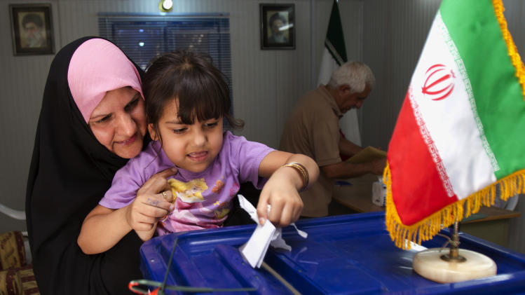 A little girl helps her mother with casting a ballot at a polling center during the presidential election in Basra, 340 miles (550 kilometers) southeast of Baghdad, Iraq, Friday, June 14, 2013. Iranian voters appeared to heed calls to cast ballots Friday in a presidential election that has suddenly become a showdown across Iran's political divide: Hard-liners looking to cement their control and re-energized reformists backing the lone moderate left in the race. (AP Photo/ Nabil al-Jurani)