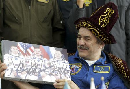 Russian cosmonaut Vinogradov holds a box of sweets during a press conference at the airport in Karaganda