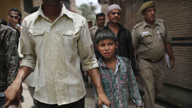 A young Indian bonded child laborer cries as he is walked away after being rescued during a raid by workers from Bachpan Bachao Andolan, or Save the Childhood Movement, at a garment factory in New Delhi, India, Tuesday, June 12, 2012. Raids on factories in the Indian capital revealed dozens of migrant kids hard at work Tuesday despite laws against child labor. Police rounded up 26 children from three textiles factories and a metal processing plant, but dozens more are believed to have escaped. Those captured had all come to New Delhi from the states of Bihar and Uttar Pradesh. (AP Photo/Kevin Frayer)