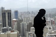A worker stands in front of a panoramic window with a view on central Caracas. Venezuela is seeing paralysis on economic decisions on the government's part, says economist Orlando Ochoa, a professor at Universidad Catolica Andres Bello.