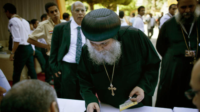 A Coptic clergyman registers for voting with election workers during the new Coptic Pope elections at the main Coptic cathedral in Cairo, Egypt, Monday, Oct. 29, 2012. A council of Egypt's Coptic Christians is voting Monday in a process that will elect a new spiritual leader for the ancient church as the community struggles to assert its identity and role amid a rising tide of Islamism that has left many Copts fearful for their future. (AP Photo/Nasser Nasser)