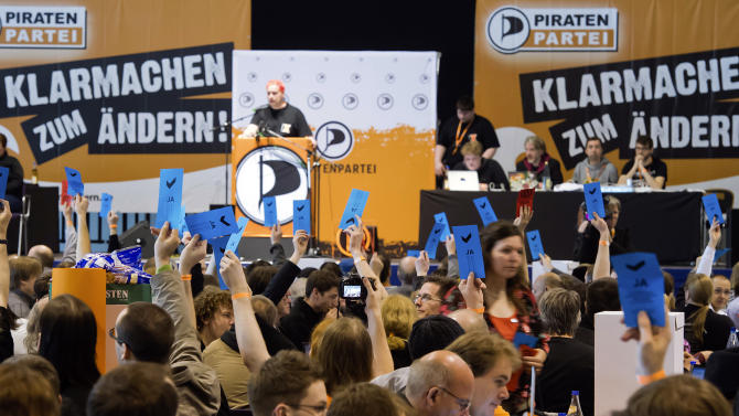 "Members of the Pirates party vote during their party convention in Neumuenster, northern Germany, Saturday, April 28, 2012. Pirates are capturing Germany's political system: The party started as a marginal club of computer nerds and hackers, but its appeal as an anti-establishment movement has lured many young voters to the ballot boxes, gaining it parliamentary seats in two consecutive state elections. Slogans in the background left and right read: ""Get Reay for Changing"". (AP Photo/dapd, Clemens Bilan)"