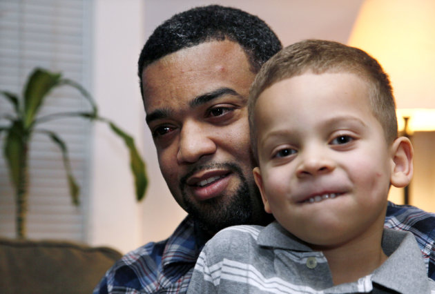 In this Dec. 27, 2011 photo, Damon Brown sits with his son Julian, 5, at their home in Seattle. Damon Brown found a kidney on Facebook after telling his story on a special page the Seattle dad created under the name, Damon Kidney. His friends and family forwarded the link to everyone they knew and on Jan. 3, a woman his wife has known for years but not someone they consider a close family friend, will be giving him a kidney. (AP Photo/Elaine Thompson)