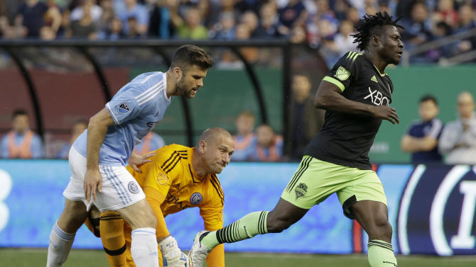 Seattle Sounders FC's Obafemi Martins, right, looks after his goal while New York City FC's Chris Wingert, left and goalkeeper Josh Saunders look on during the first half of an MLS soccer game at Yankee Stadium in New York, Sunday, May 3, 2015. (AP Photo/Seth Wenig)