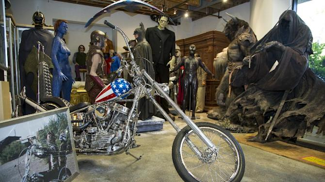 "This Thursday, Sept. 4, 2014 photo shows the Captain America chopper Peter Fonda rode in ""Easy Rider"" surrounded by Hollywood memorabilia at the Profiles in History auction house in Calabasas, Calif. The bike features a forward-angled front wheel and handlebars, fishtail exhaust pipes and a teardrop-shaped gas tank where the protagonists stashed their cash. The auction house Profiles in History tells The Associated Press it estimates the Harley-Davidson will bring between $1 million and $1.2 million at its Oct. 18, 2014 sale. (AP Photo/Damian Dovarganes)"