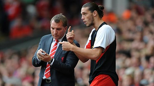 Liverpool's manager Brendan Rodgers speaks to Andy Carroll
