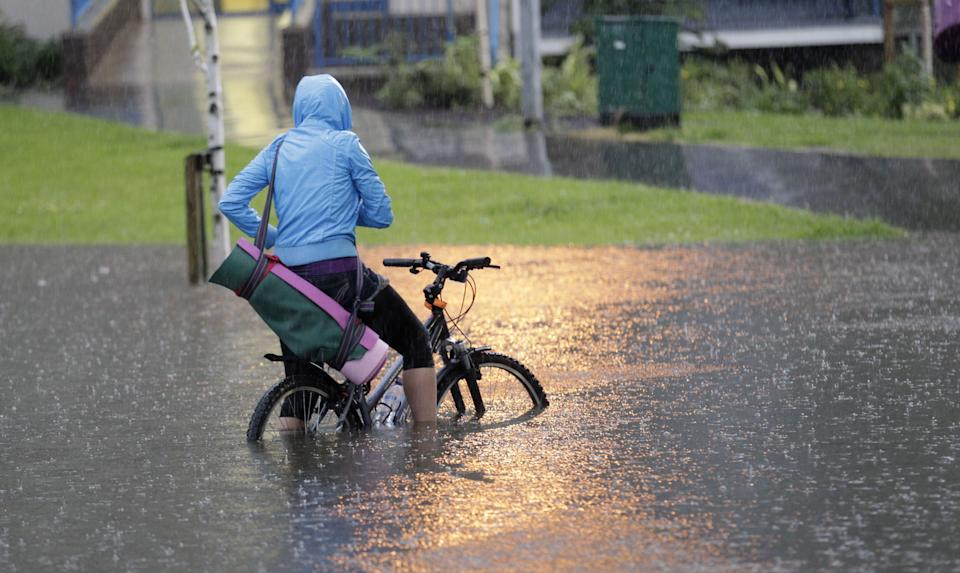 A cyclist tries to make her way through a flooded road in heavy rainfall in the Cregagh estate in East Belfast, Northern Ireland, Wednesday, June 27, 2012. (AP Photo/Peter Morrison)