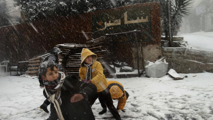 Palestinians enjoy a snowball fight in the southern West Bank village of Halhoul, Wednesday, Jan. 9, 2013.  A Palestinian official says the fiercest storm to hit the area in a decade has claimed the lives of two West Bank women who drowned after their car was caught in a flash flood unleashed by torrential rains. (AP Photo/Nasser Shiyoukhi)