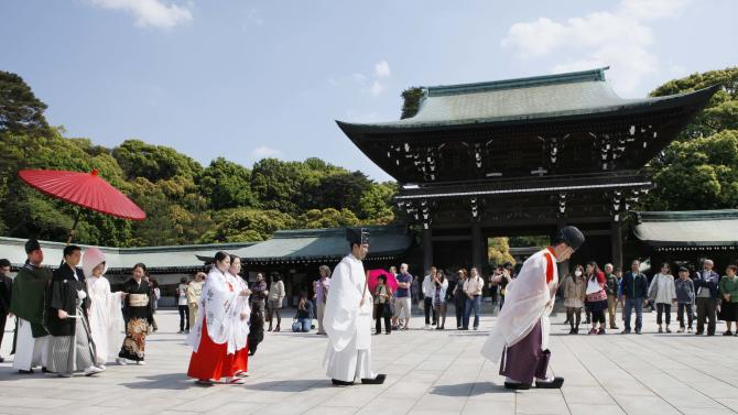"""In this Saturday, May 4, 2013 photo, Shinto priests lead a Japanese couple under a parasol during a traditional wedding ceremony at Meiji Jingu Shrine in Tokyo. Meiji Jingu Shrine is a piece of old Tokyo not to be missed. Boasting the nation's largest wooden """"torii"""" gate, the shrine was built more than 90 years ago to commemorate Emperor Meiji, who reigned as Japan opened to the rest of the world after centuries of isolation. (AP Photo/Koji Sasahara)"""