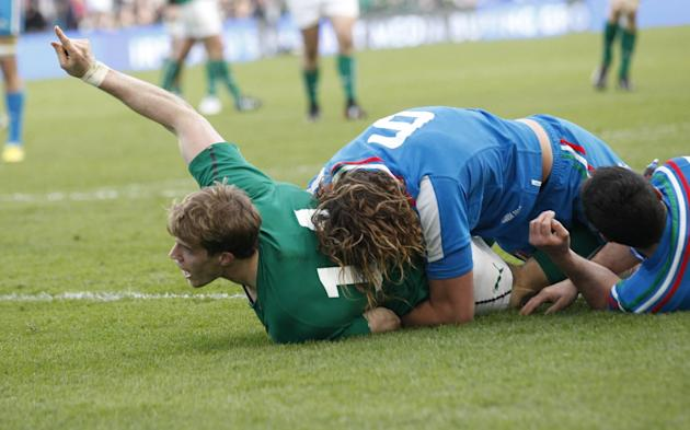 Ireland's Andrew Trimble left, scores a try despite being tackled by Italy's Joshua Raffaele Furno during their Six Nations Rugby Union international match at the Aviva Stadium, Dublin, Irelan